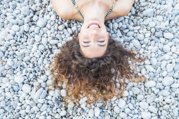 An overhead view of smiling young woman laying on pebbles