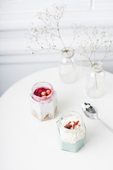 An overhead view of smoothies jar; spoon and vase on table