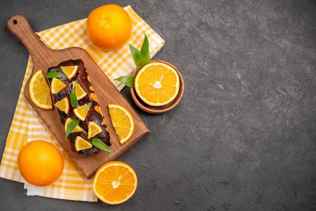 Vista dall'alto di torte morbide e arance tagliate con foglie sul tavolo scuro