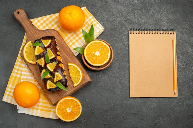 Overhead view of soft cakes whole and cut lemons with leaves next to notebook on dark table