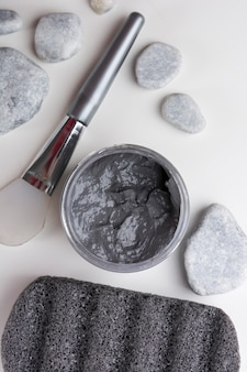 An overhead view of spa stones; brush; clay mask; and pumice stone on white background