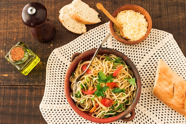 An overhead view of spaghetti pasta on earthenware with cheese and bread on wooden table