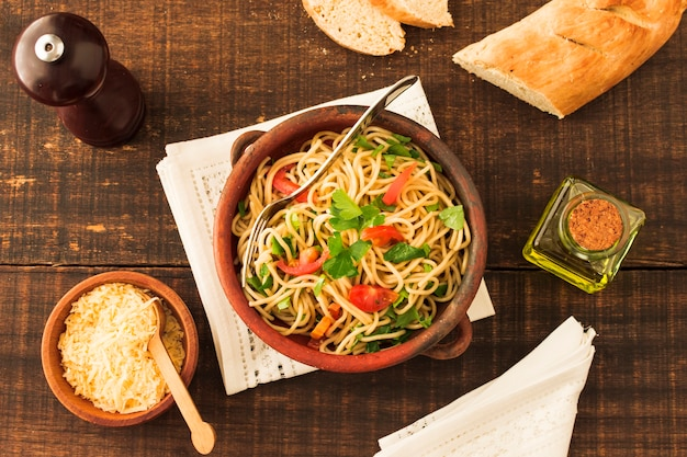 An overhead view of spaghetti pasta with cheese and bread on wooden table