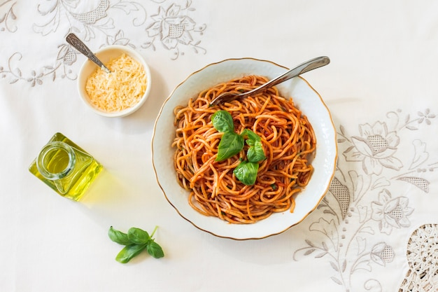 An overhead view of spaghetti with cheese bowl; basil and olive oil on tablecloth