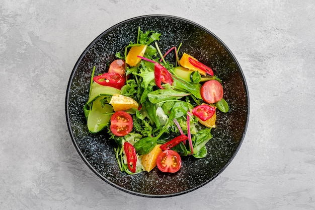 Overhead view of spicy salad with orange, chilli pepper, tomato, cucumber and avocado