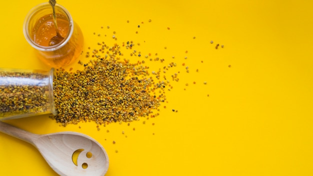 An overhead view of spilled bee pollens; honey pot and smiley wooden spoon on yellow backdrop