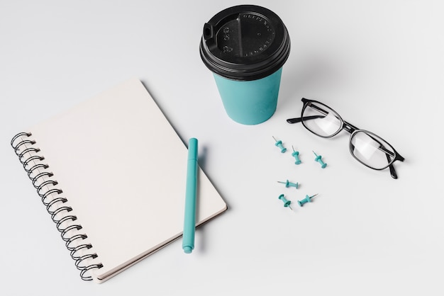An overhead view of spiral notebook; pen; spectacles; disposable coffee cup; and pushpin on white background