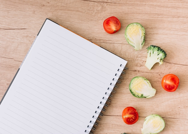 An overhead view of spiral notebook with brussel sprouts; tomatoes and broccoli on wooden table