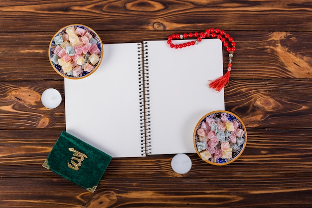 An overhead view of spiral notebook with delight lukum bowls; kuran and red prayer beads on wooden desk