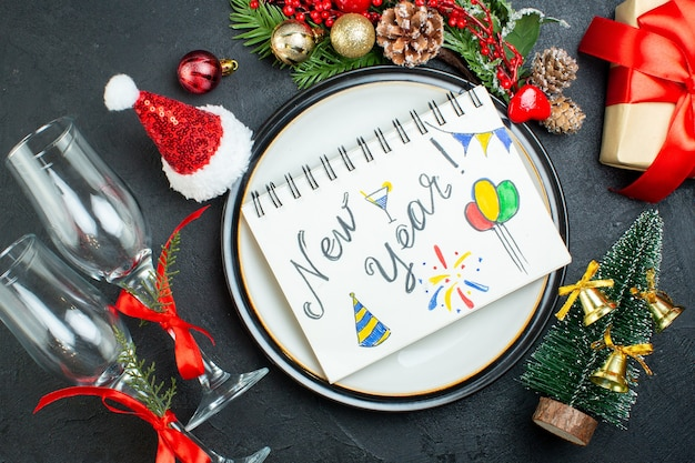 Overhead view of spiral notebook with pen on dinner plate christmas tree fir branches conifer cone gift box santa claus hat fallen glass goblets on black background