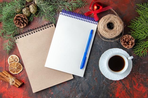Vista dall'alto di quaderni a spirale con penna abete branche cannella limes cono di conifere e una tazza di tè nero su sfondo scuro