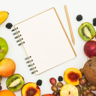An overhead view of spiral notepad; pencil and various fruits on white backdrop