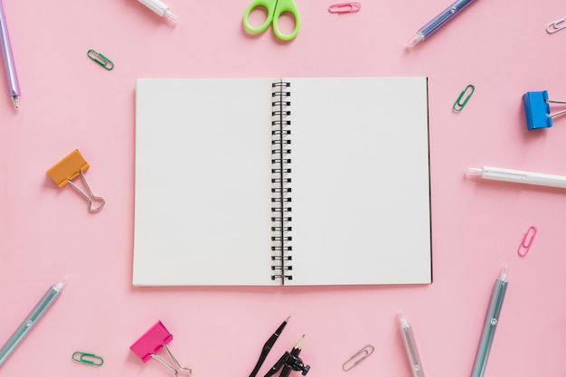 Overhead view of spiral notepad surrounded by various stationeries on pink backdrop
