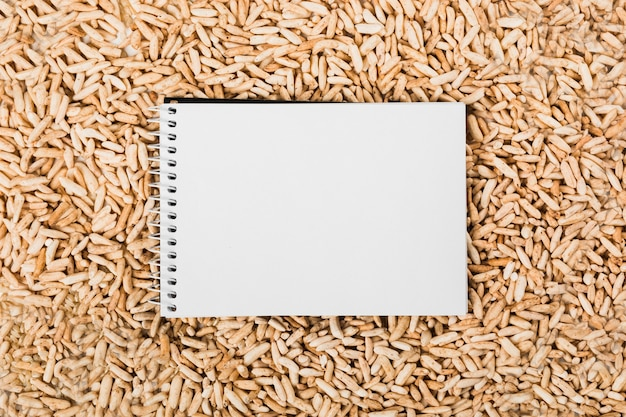 An overhead view of spiral white notepad over the brown puff rice