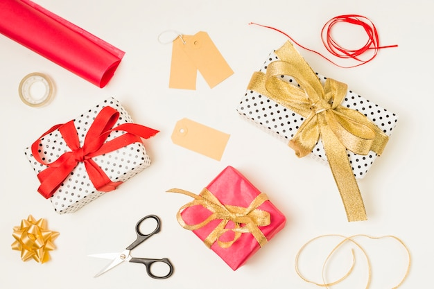 Overhead view of stationery supplies; gift boxes and blank labels on white background
