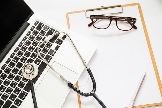 Overhead view of stethoscope on an open laptop with clipboard and eyeglasses on white background