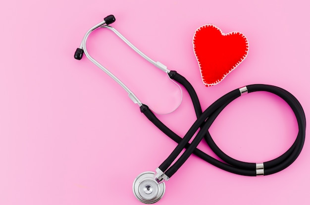 An overhead view of stethoscope with red textile heart on pink backdrop