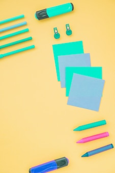 Overhead view of sticky note; highlighter and crayons on yellow background