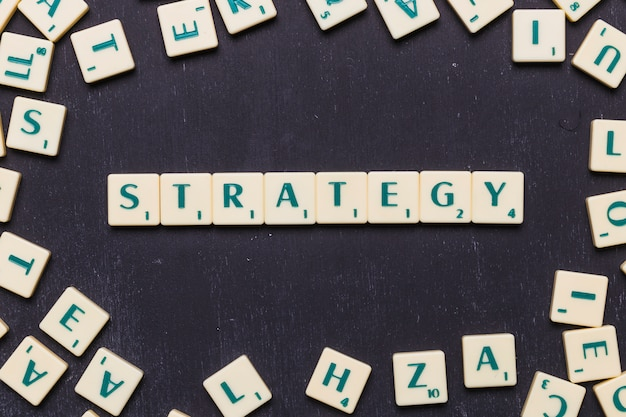 Overhead view of strategy text on scrabble letters over black backdrop