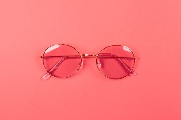 An overhead view of sunglasses on coral background
