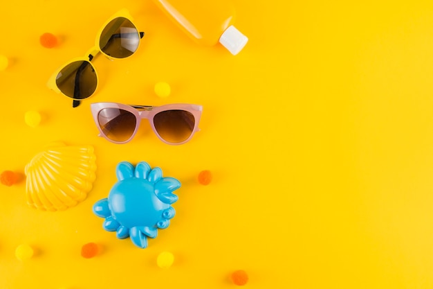 An overhead view of sunglasses; sunscreen lotion bottle; scallop and crab toy on yellow backdrop