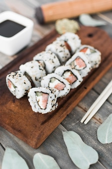 An overhead view of sushi roll on wooden tray with soya sauce and chopstick on wooden table