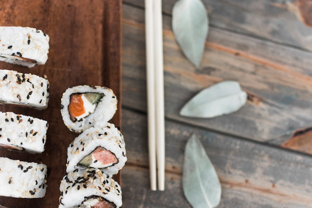 An overhead view of sushi on with chopsticks over the table