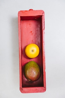 Overhead view of sweet lime and mango in wooden container