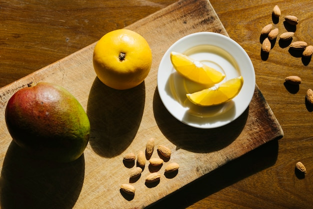 Overhead view of sweet lime and mango on wooden cutting board