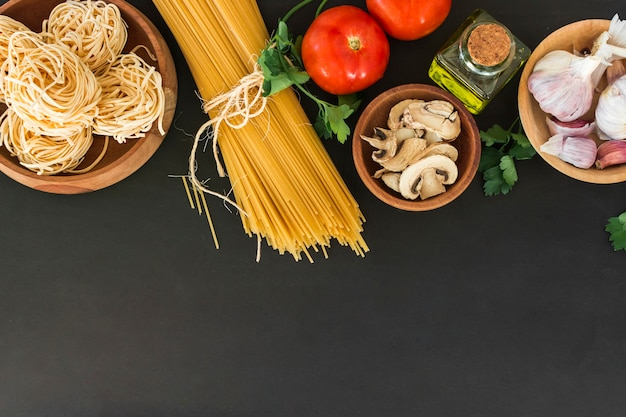 An overhead view of tagliatelle and spaghetti pasta with ingredients on black background