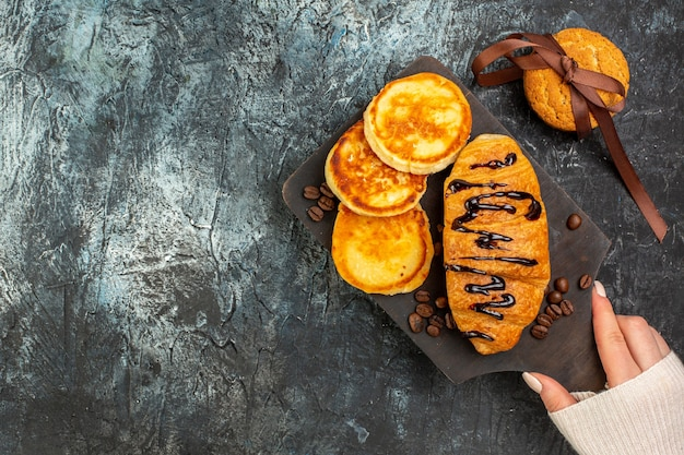 Overhead view of tasty breakfast with pancakes croisasant stacked cookies on dark background