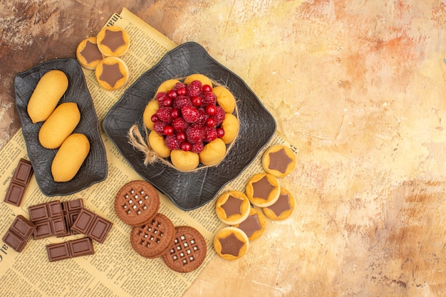Overhead view of tasty cake different biscuits on brown plate on mixed color table
