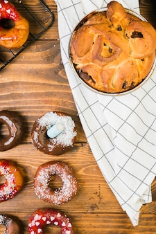 Overhead view of tasty dessert and chocolate donut on wooden desk