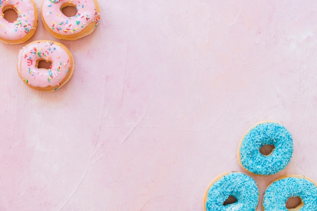 Overhead view of tasty donuts on pink backdrop