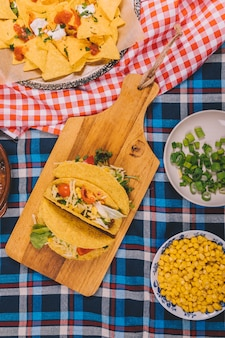 Overhead view of tasty mexican nachos and tacos on table cloth