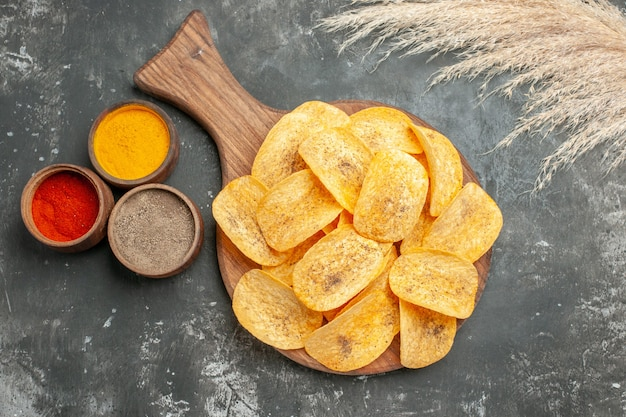Overhead view of tasty potato chips spices with ketchup on gray table