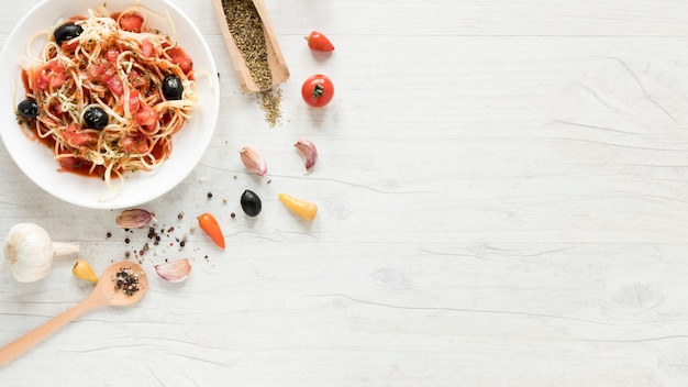 Overhead view of tasty spaghetti pasta and fresh aromatic ingredients on table