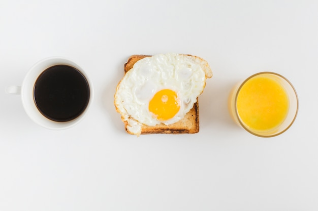 An overhead view of tea cup; juice glass and toast bread with fried egg isolated on white backdrop