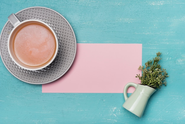 An overhead view of tea cup with blank pink paper and vase on blue texture backdrop