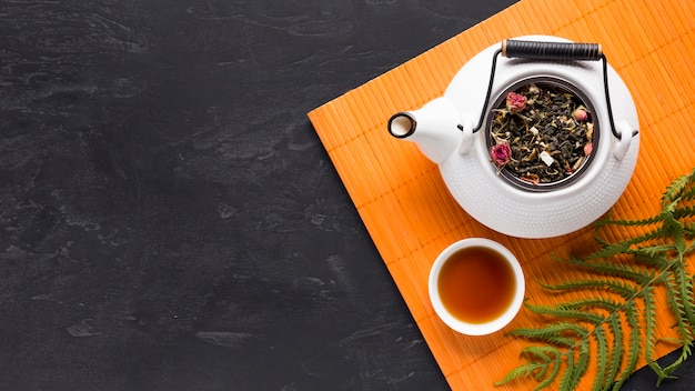 Overhead view of tea herb and teapot with fern leaves on orange placemat over black backdrop