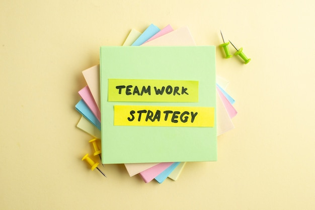 Vista aerea della strategia di lavoro di squadra scrivendo su uno dei cubi di nota adesiva impilati su sfondo giallo ombreggiato con spazio libero
