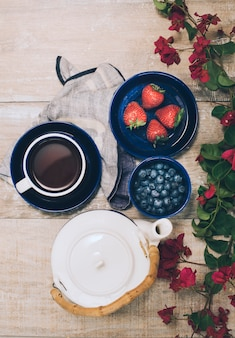 An overhead view of teapot; coffee cup; strawberries and blueberries on wooden plank
