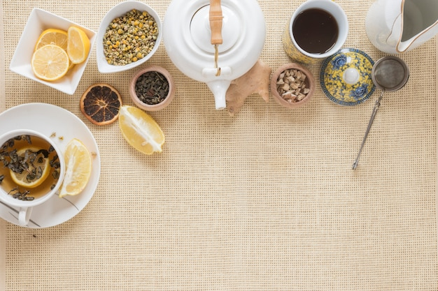 Overhead view of teapot; tea strainer; lemon slice; dry grapefruit and dried chinese chrysanthemum flowers on placemat