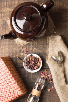 An overhead view of teapot with dried herbs; wicker box; strainer and jute on wooden desk