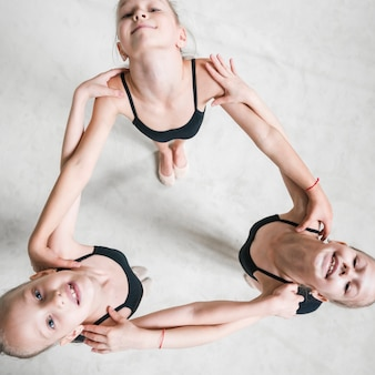 Overhead view of three ballerina girls holding each other's shoulder looking up