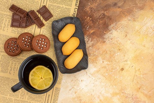 Vista dall'alto di tre biscotti e tè in una tazza nera sulla tavola di colori misti