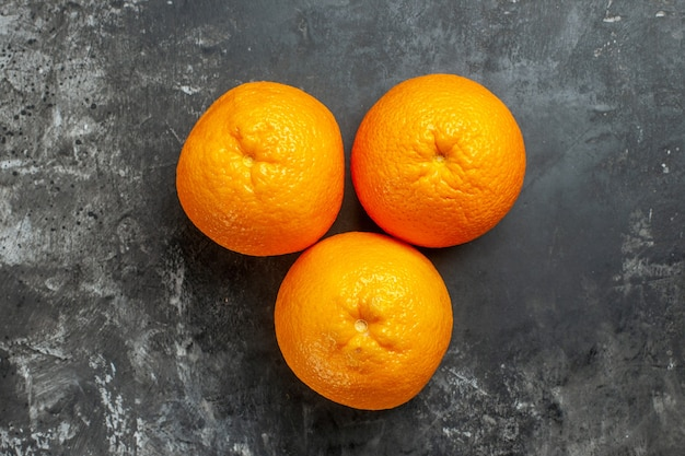 Vista dall'alto di tre arance fresche organiche naturali su sfondo scuro