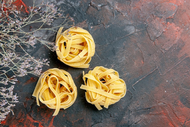 Overhead view of three uncooked spaggeties on mixed color table