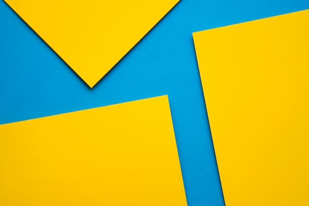 Overhead view of three yellow craftpapers on blue background