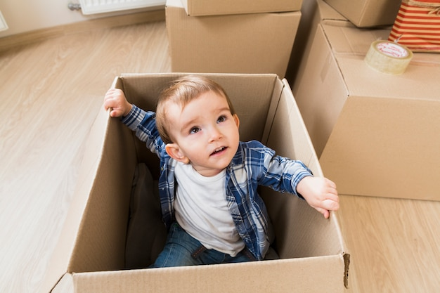 An overhead view of a toddler boy sitting inside the cardboard box looking up